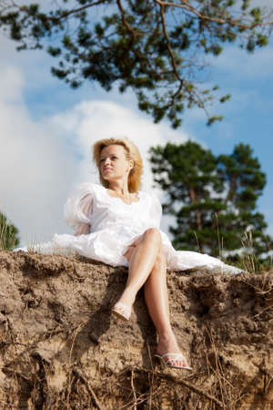 far away look: on the edge.beautiful woman in white dress sitting on the edge of a precipice