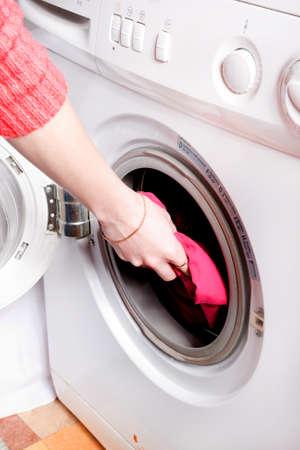 Young woman loading the washing machine