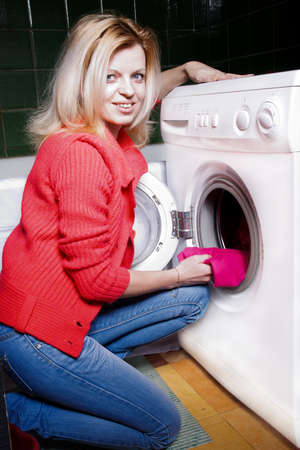 Young woman loading the washing machine photo