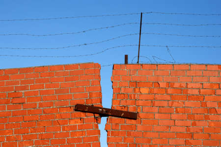 Red Brick broken Wall with barbed wire against blue sky photo