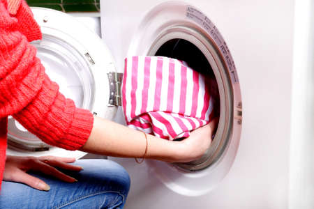 Woman load clothes in a washing machine