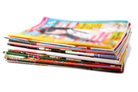 a stack of old colored magazines on white