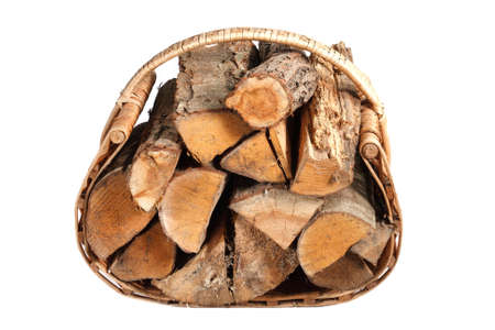 chopped firewood in wicker basket on a white background Stock Photo