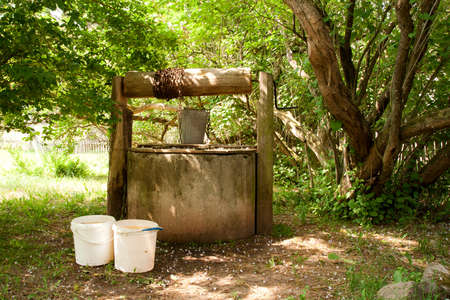 an old water well in the shade of trees Stock Photo