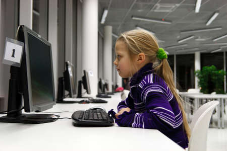 serious little girl used a public library computer