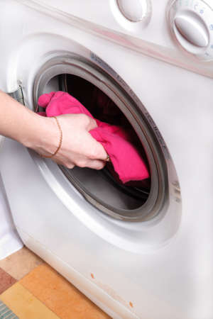 womans hand puts the laundry in washing machine photo