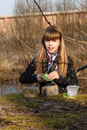 A young Girl writes in the logbook of a small geocache he just found.  Geocaching is a worldwide treasure hunting game where a GPS is used to locate different sized containers containing a logbook and small goodies.