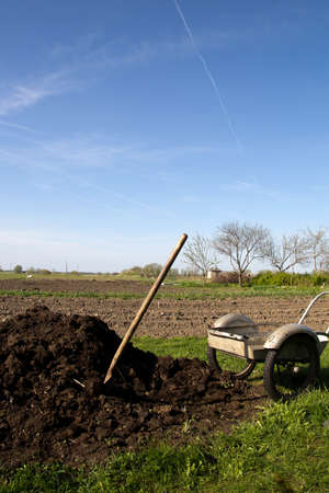 Spring view of the garden with a organic fertilizer pile and wheelbarrow Stock Photo