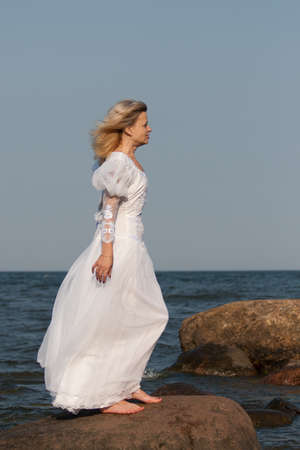 woman in white dress standing on a large stone at the beach photo