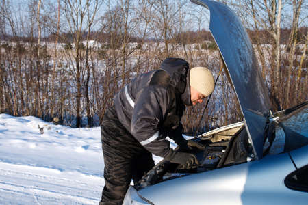 man checked the broken car engine in cold winter day Stock Photo