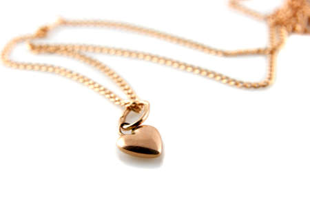locket: Gold heart pendant with chain on white background Stock Photo
