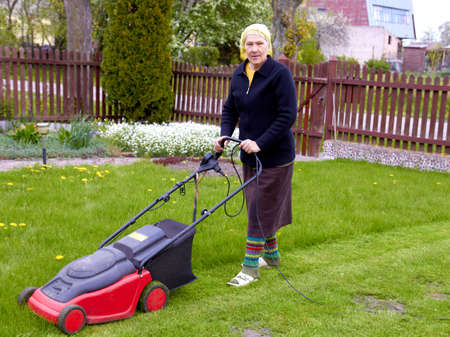 senior woman working with lawn mower in his garden photo