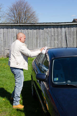 Man washing car in a countryside outdoors photo