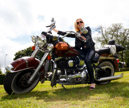 Girl dressed in leather clothes on big motorcycle photo