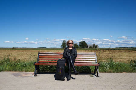 lonely bus stop at countryside with women on bench photo