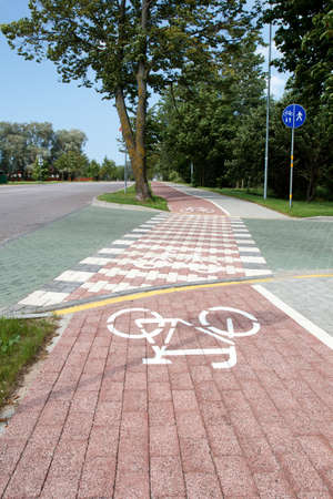 paved bicycle path crosses the street photo