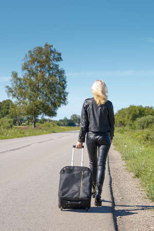 woman dressed in leather clothes walking along the rural roadside Stock Photo