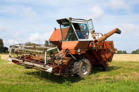 old grain harvester still working on the field photo