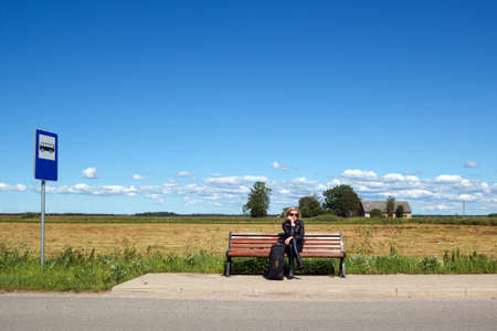 tourists stop: lonely bus stop at countryside with women on bench