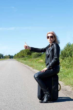 vrouw lift op een eenzame weg met haar duim omhoog