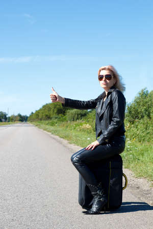 hitchhiking: woman hitchhiking on a lonely road with her thumb up