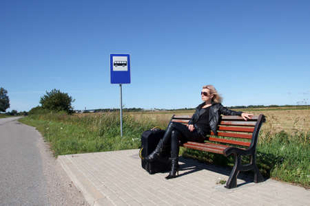 tourists stop: lonely woman sitting on a bench at a bus stop in the countryside