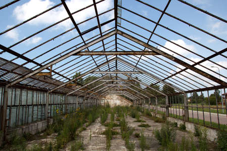 without windows: old abandoned greenhouse without windows against blue sky Stock Photo