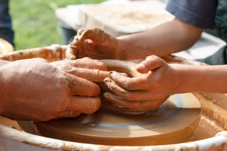 master and apprentice. Potters and child hands photo