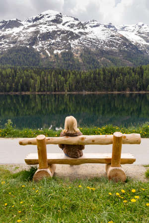 enjoying nature, girl sitting on a bench near the lake and looks on big mountains Stock Photo - 15336022