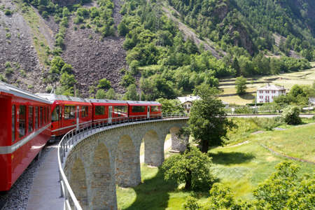 Swiss mountain train Bernina Express  passes the spiral of the Brusio Viaduct Stock Photo - 15347223