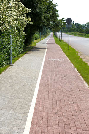 Paved sidewalk with a bicycle path photo