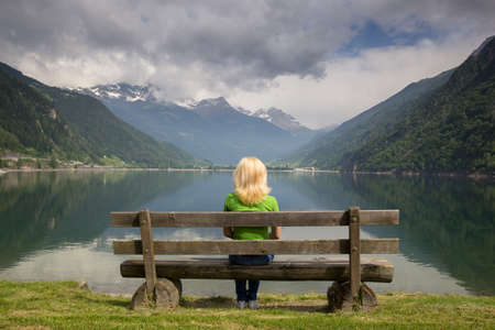 bench in the high mountains at the lake Poschiavo, Switzerland Alps photo
