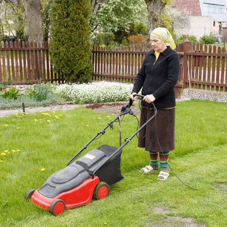 mowing grass: senior woman mowing grass with electric mower in his flower garden