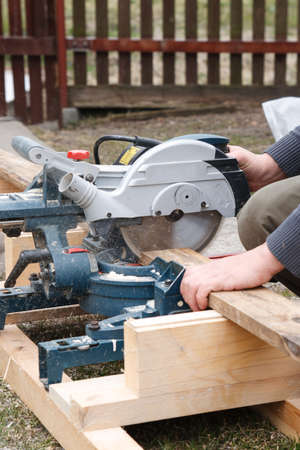Carpenter sawing board with an electric circular saw photo