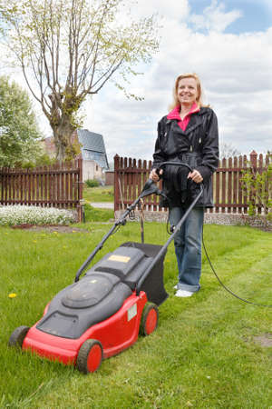 Woman mowing a garden with an electric lawn mower photo