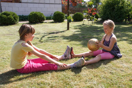 entre filles: Deux petites filles jouant avec une balle dans le jardin