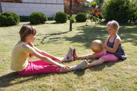 ni�as jugando: Dos ni�as jugando con una pelota en el jard�n