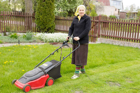 mowing grass: old woman mowing grass with an electric mower