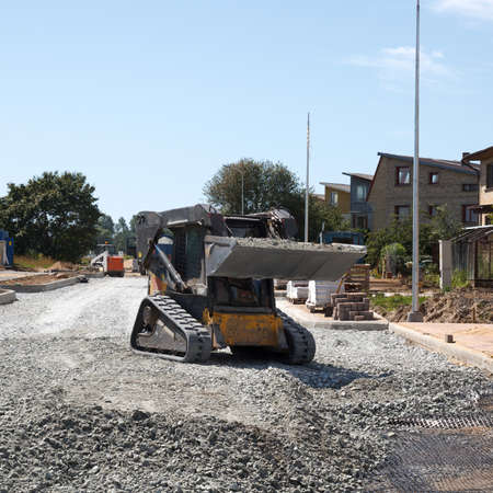 road surface: construction of a new street. mini excavator bobcat mowing breakstone