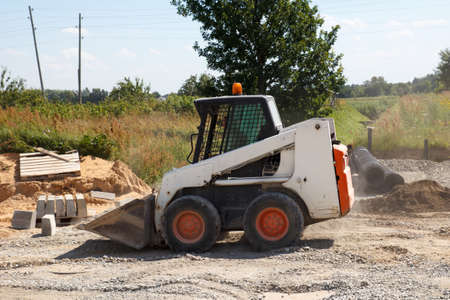 excavate: mini excavator bobcat working in construction site, making new street