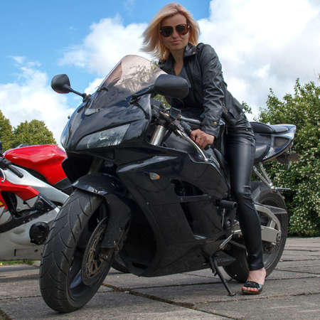 biker girl dressed in leather clothes a black motorcycle photo