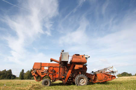 old grain harvester working in a field photo