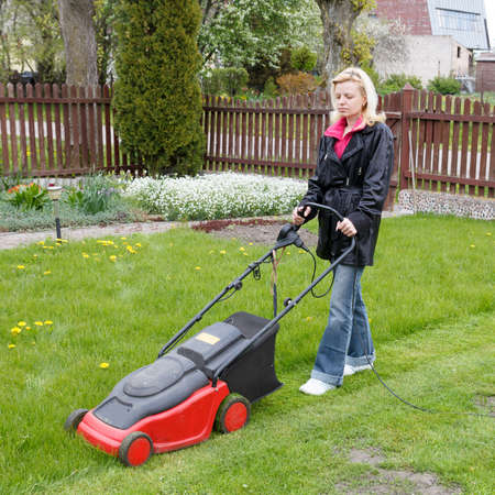mowing grass: woman mowing grass with an electric lawn mower Stock Photo