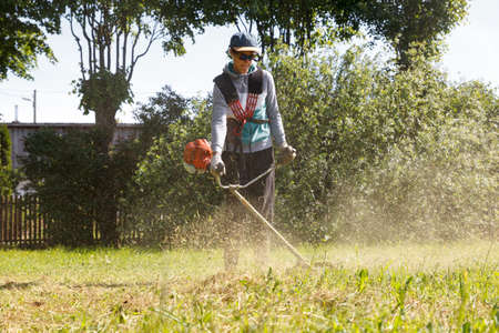 a man cut the grass with a lawn trimmer Stock Photo