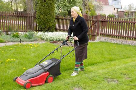 yard work: old woman mowing grass with an electric mower
