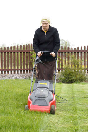 old woman mowing grass with an electric mower photo