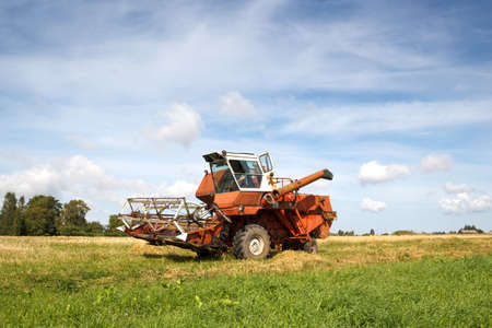 old grain harvester still working in the field Stock Photo - 16615340