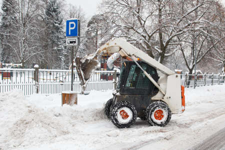 small excavator bobcat working on the street, cleaning snow Stock Photo - 16935799