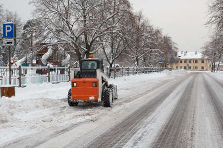 small excavator bobcat working on the street, cleaning snow Stock Photo