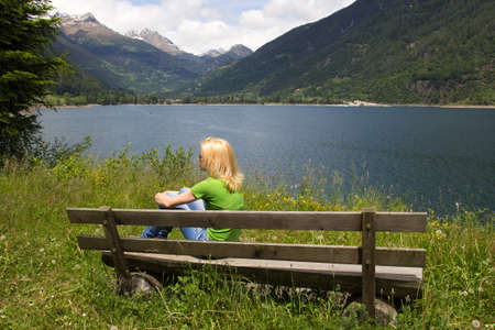 Woman resting on a bench near the lake Poschiavo in the Swiss Alps